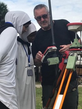 (Figure 3. Nick Pearson showing the GPS and base station to two students from a local school who where learning a method called chain surveying!)