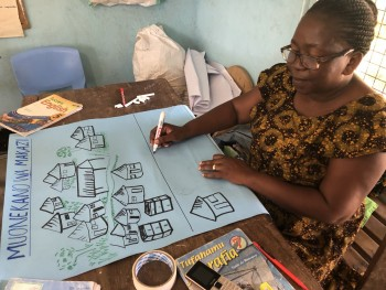 Harieth from Pangani Primary prepares a poster showing various settlement types